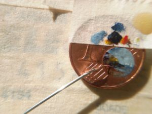 Il supporto (una monetina da un centesimo), il pennello (una penna di un volatile infilato dentro la cavità di un ago di siringa) e la mia tavolozza (uno spezzone di nastro di carta adesiva) aderente al cent che contiene i colori da stendere.